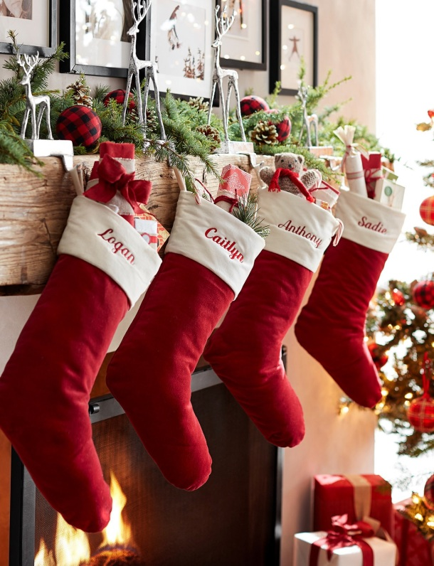 Personalized Christmas Stockings, red with white cuffs, hanging from deer stocking holders